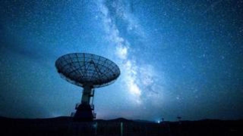 A radio telescope against a night sky