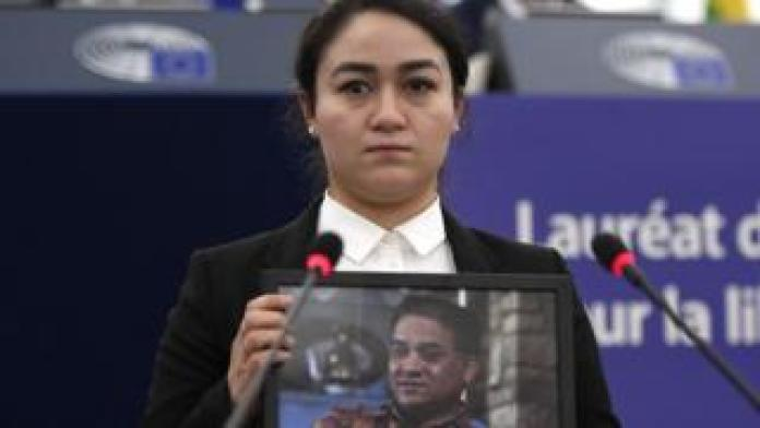 Jewher Ilham holding a portrait of her father, Ilham Tohti, during the award ceremony on December 18