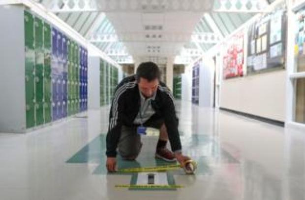 Social distancing tape is placed on a one way sign in a corridor, as preparations are made for the new school term at Alderwood School in Aldershot, Hampshire 26 August 2020