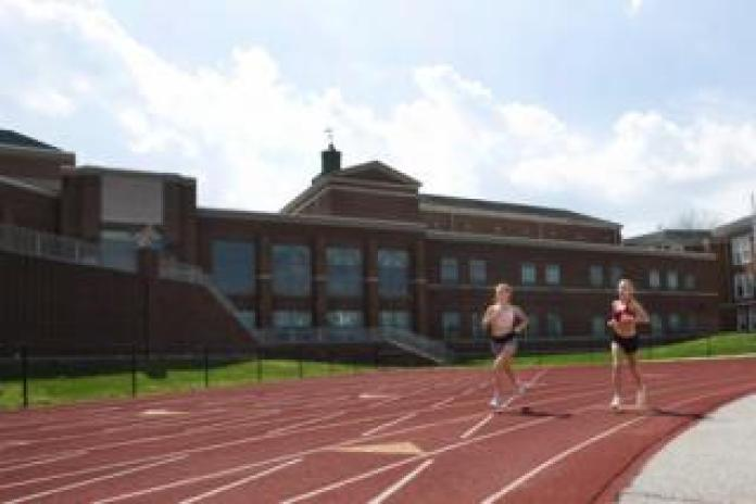 Maddie's sister Sabina runs on an empty track with her friend