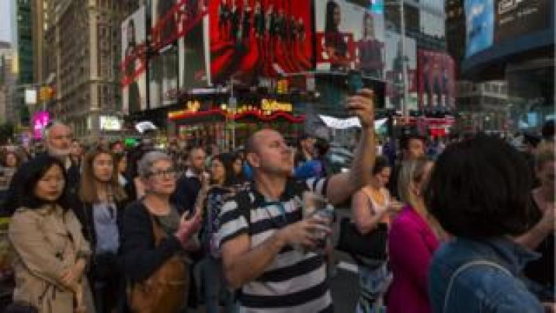 People take pictures of the phenomenon known as Manhattanhenge on Times Square