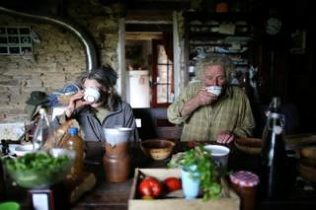 Laurence and Jean-Bernard sip from cups in their farmhouse