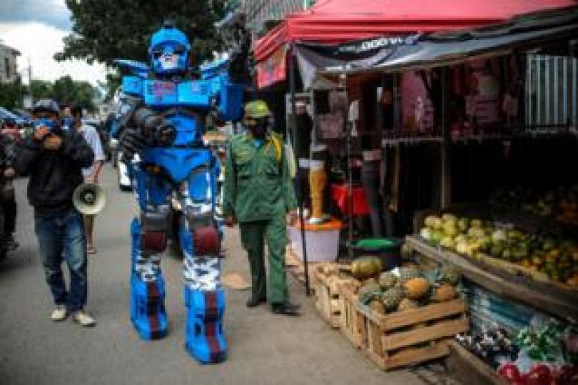 A man wearing a Transformers costume walks past a food stall
