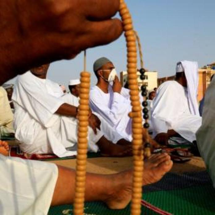 Man in facemask praying in Khartoum
