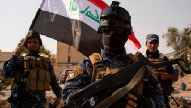 Iraqi federal police officers wave a national flag as they celebrate in Mosul's Old City on 9 July 2017