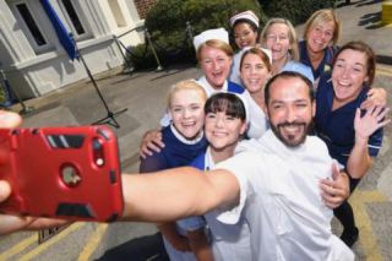 Nurses in uniforms take a selfie photo outside Trafford Hospital