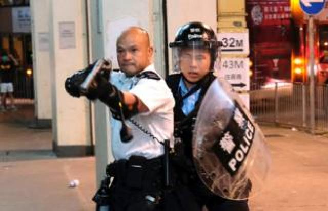 A police officer points a gun towards anti-extradition bill protesters