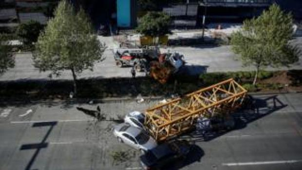 Police inspect cars crushed by part of a construction crane in Seattle, Washington, April 27, 2019