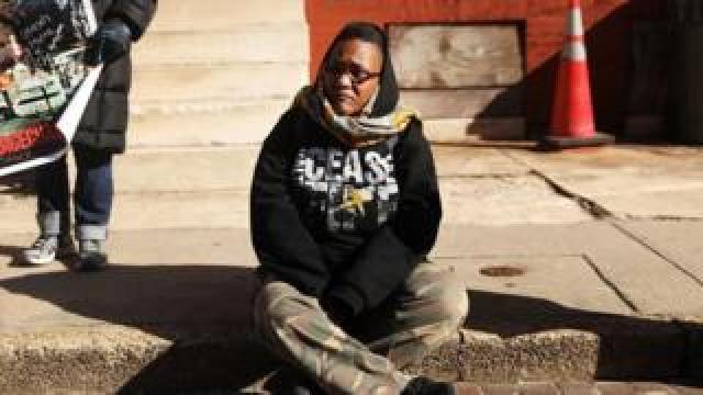 Erricka Bridgeford sitting on the sidewalk where her son was killed
