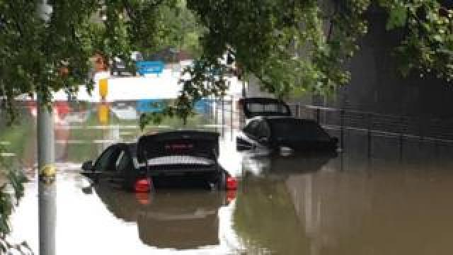two cars stuck on flooded road