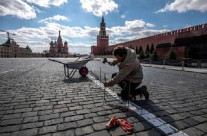 A man mends paving stones in Red Square