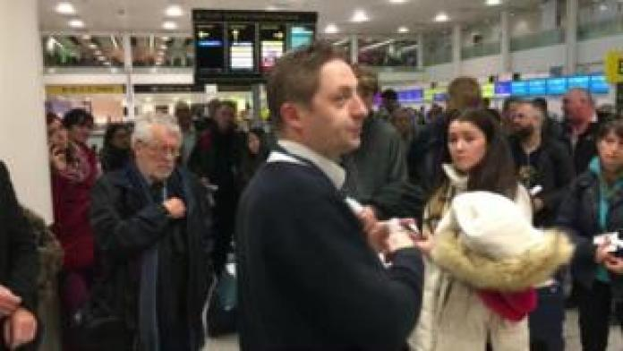 A member of airport staff addresses a crowd of passengers