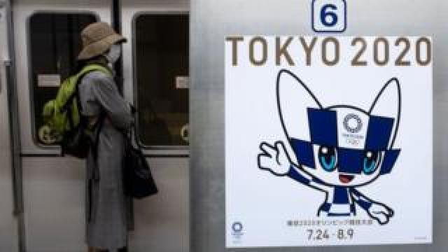 A passenger wearing a face mask stands next to a poster of Tokyo 2020 Olympic mascot Miraitowa on a train in Tokyo on April 20, 2020