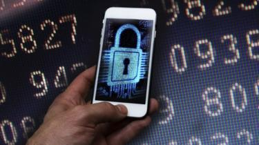 Imagem de um hacker usando um telefone celular para roubar dados
