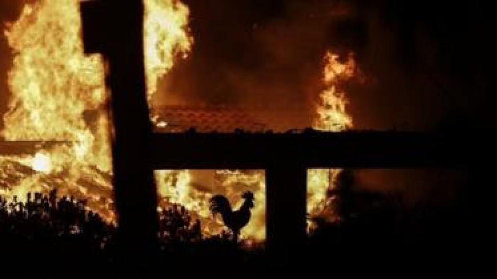 A rooster decoration in a burning house is seen during a forest fire in Mati a northeast suburb of Athens, Greece, 23 July 2018