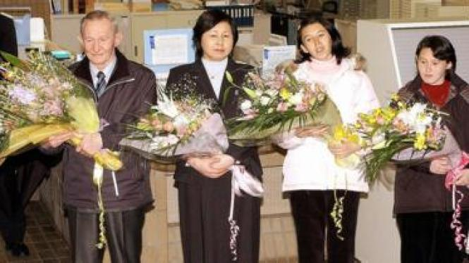 US army deserter Charles Jenkins (L), accompanied by his wife Hitomi Soga (2nd L) and daughters Mika (2nd R) and Brinda (R), receives flower bouquets upon his arrival at Sado island in Niigata prefecture, 300km north of Tokyo, hometown of his Japanese wife Hitomi Soga as he left a US base 7 December 2004.