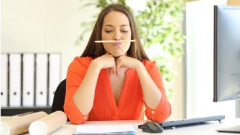 Mujer de pelo largo con un lápiz entre boca y nariz