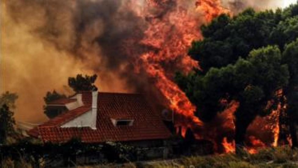 A house is threatened by a huge blaze during a wildfire in Kineta, near Athens, on July 23, 2018