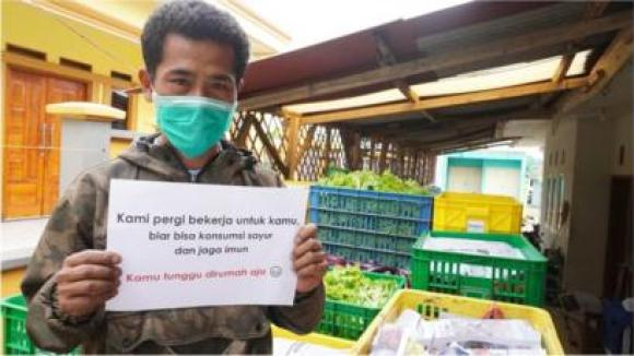 """Farmer Pak Opik holds up a sign that says """"We go to work for you, so you can have vegetables to stay healthy"""""""