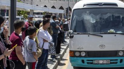 Residents queue for a bus after the Jordanian government started to ease the lockdown, 10 May 2020
