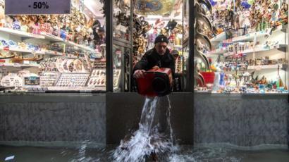 Un commerçant utilise un seau pour retirer l'eau de sa propriété à Venise, 13 novembre 2019