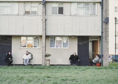 People sitting outside their homes