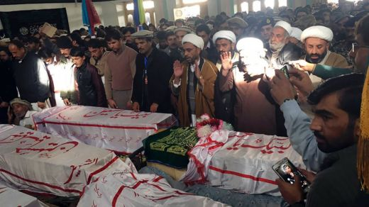 Pakistani mourners offer funeral prayers, gathered around coffins of the blast victims in Parachinar