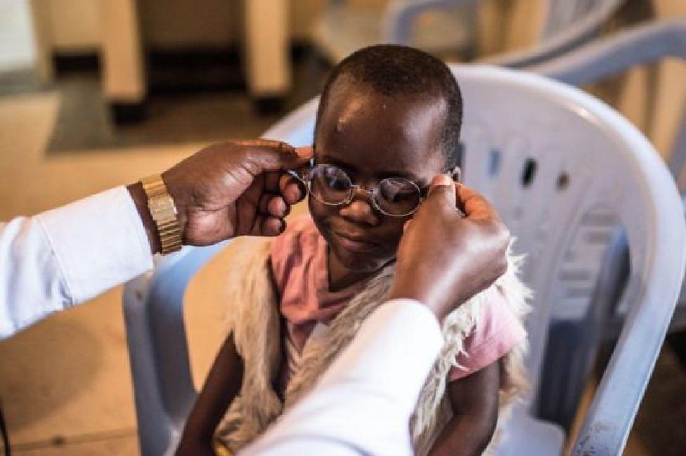 Un doctor le pone los lentes a Criscent por primera vez.