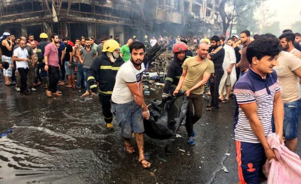 Iraqi firefighters and civilians carry bodies of victims killed in a car bomb at a commercial area in Karrada neighbourhood, Baghdad, Iraq, Sunday, July 3, 2016