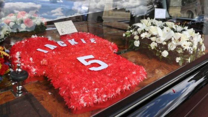 Floral tribute in the shape of a red England shirt bearing the number 5