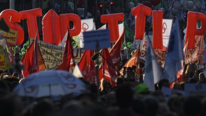 People hold balloons reading 'Stop TTIP' during a demonstration outside the European Union headquarters in Brussels, on September 20, 2016