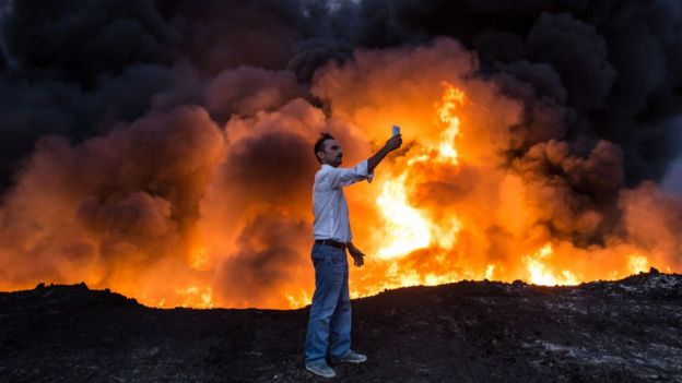 A man takes a selfie in front of flames south of Mosul