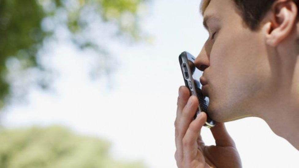 Hombre besa un celular.