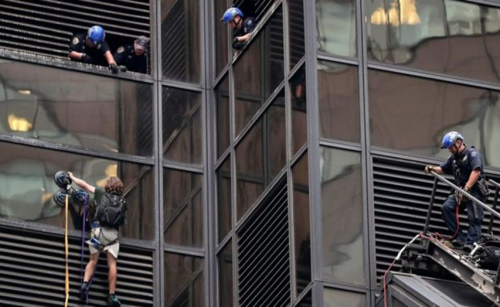 A man scales the all-glass facade of Trump Tower