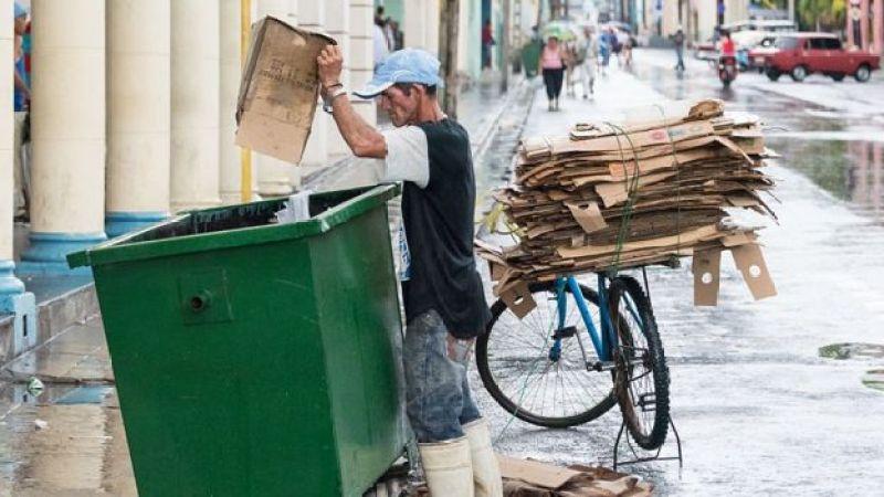 Hombre sacando cartones de la basura