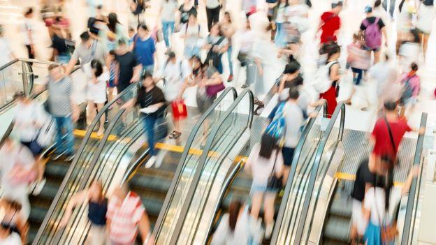 Pessoas subindo e descendo escada-rolante de shoppping