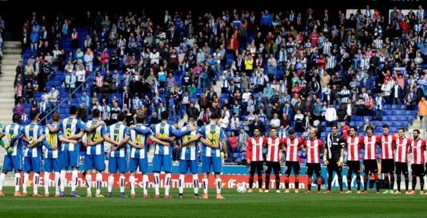 Players of Espanyol (L) and Athletic Bilbao (R) observe a minute of silence in tribute to the victims of a bus crash