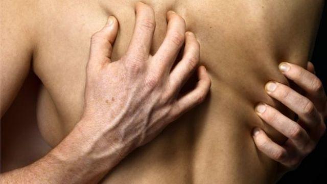 Manos aprietan una espalda desnuda de mujer