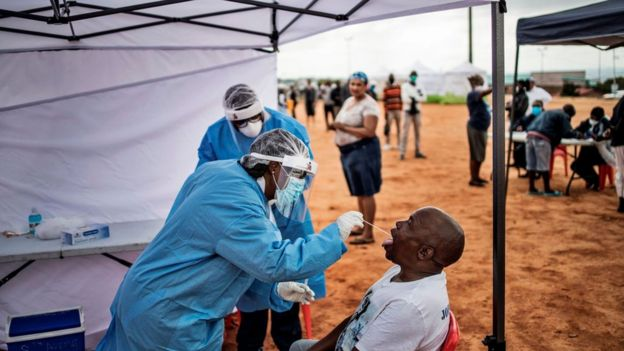 A man, a resident of the sprawling township of Alexandra in Johannesburg, opens his mouth to receive a testing swab for COVID-19 coronavirus at a screening and testing drive in front of the Madala Hostel, on April 27, 2020.