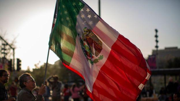 Un hombre sostiene las banderas de México y Estados Unidos.