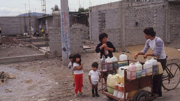 Mujer vendiendo bebidas en un barrio popular en México.