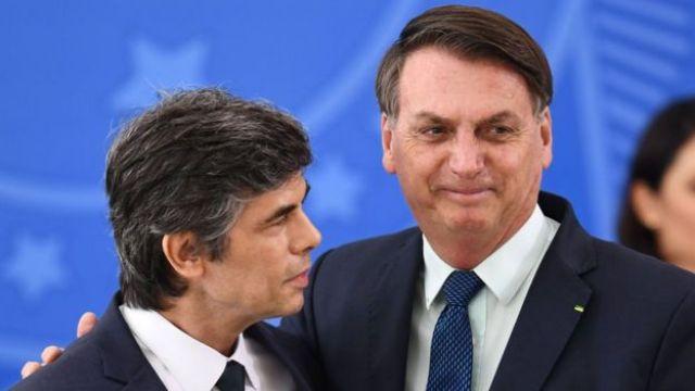 O ex-ministro Nelson Teich abraçado ao presidente Jair Bolsonaro, que tem um meio sorriso no resto, em foto antes da demissão