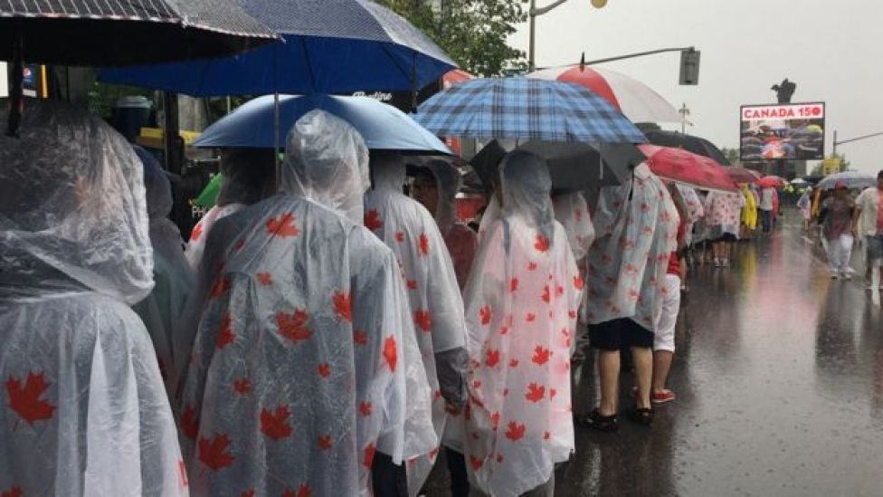 Canadians queue in the rain on Canada Day
