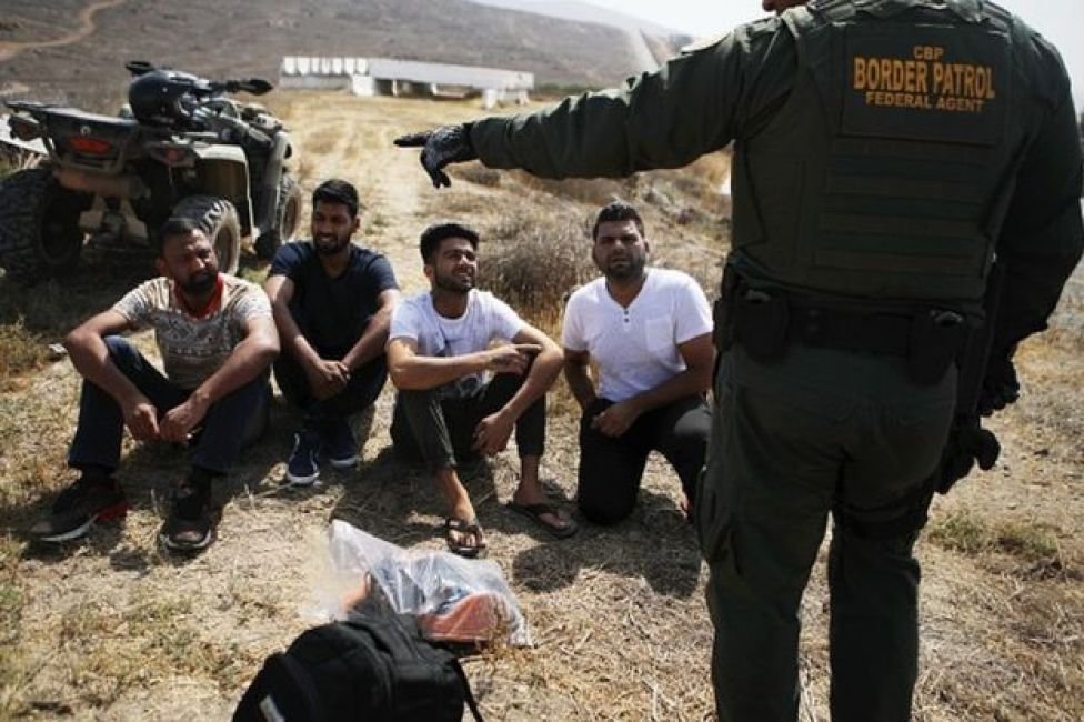 A U.S. Border Patrol agent monitors a group of apprehended males from India who illegally crossed the U.S.-Mexico border on July 16, 2018 in San Diego, California. The entire Southwest border saw 34,114 U.S. Border Patrol apprehensions in the month of June compared with 40,338 in May.