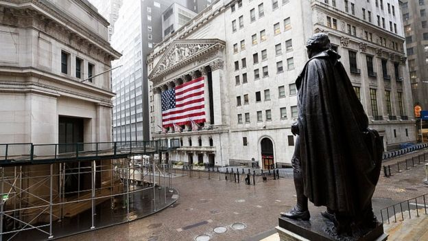 A quiet Wall Street with a view of a statue of George Washington and the New York Stock Exchange in New York, 13 April 2020