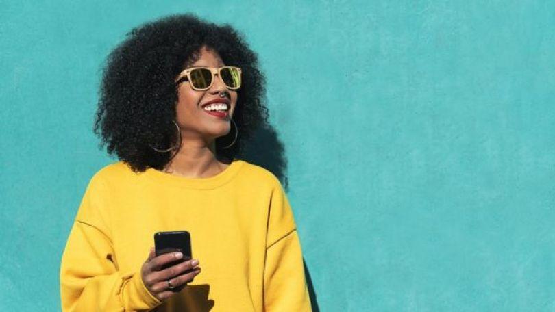 Mulher com cabelo black, óculos escuros, moletom amarelo e celular na mão - o uso de celular gera milhares de dados pessoais, nas mãos de empresas