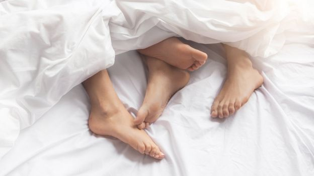 Dos pares de pies en una cama.