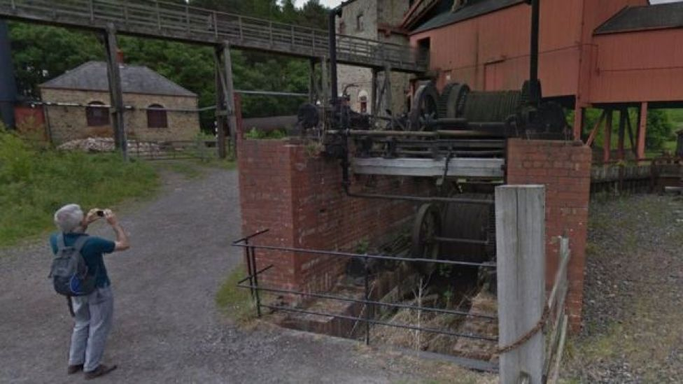 A man takes a picture of old mine workings