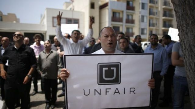 """A man holds a sign saying """"Uber Unfair"""" at a protest in California"""