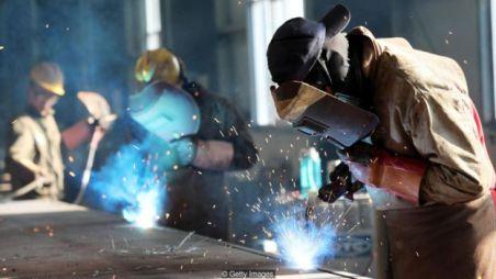 Homens trabalham usando maçaricos em indústria